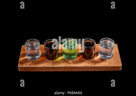 Multicolored transparent cocktails, a set of shots in one row, five servings on a wooden stand, substrate. Side view Isolated black background. Drink  - Stock Photo