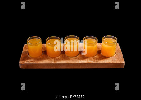 Yellow, same color opaque cocktails, a set of shots in one row, five servings on a wooden stand, substrate. Side view Isolated black background. Drink - Stock Photo