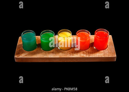 Multicolored opaque cocktails, a set of shots in one row, five servings on a wooden stand, substrate. Side view Isolated black background. Drink for t - Stock Photo