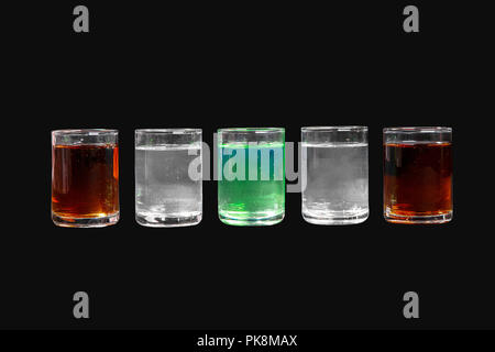 Multicolored transparent cocktails, a set of shots in one row, five servings. Side view Isolated black background. Drink for the menu restaurant, bar, - Stock Photo