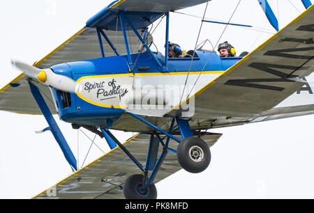 Spirit of Pashley, G-AMNN, a 2 seater single engine Tiger-Moth Bi-plane flying low as it comes into land in Southern UK. - Stock Photo