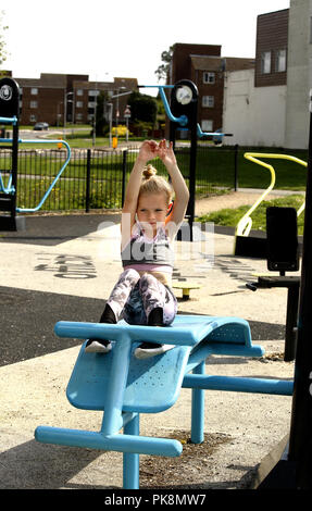 A six year old girl doing 'sit ups' on free to use equipment in an outdoor fitness area - Stock Photo