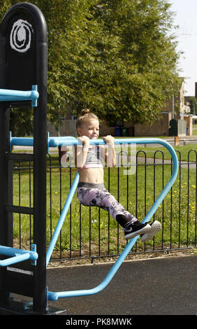 A six year old girl doing 'pull ups' on free to use equipment in an outdoor fitness area - Stock Photo