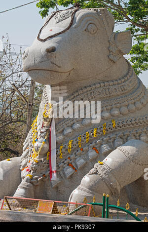 Massive granite carving of the mythical bull known as Nandi in Hindu folklore situated on Chamundi Hill on the outskirts of Mysore in Karnataka, India - Stock Photo