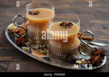Indian masala chai tea. Spiced tea with milk in a vintage cups on the rustic wooden table. - Stock Photo