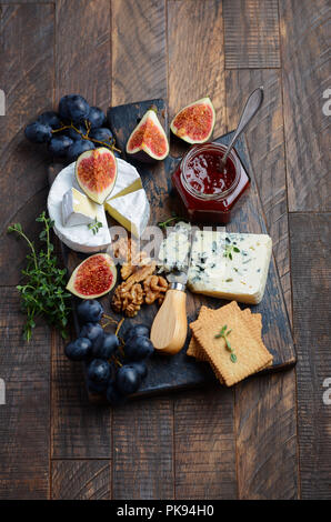 Cheese plate with grapes, figs, crackers, honey, plum jelly, thyme and nuts, selective focus. - Stock Photo