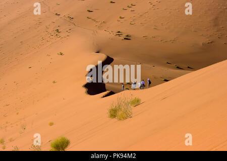 People walk on sand dunes, Sossusvlei, Namib-Naukluft Park, Namibia. - Stock Photo