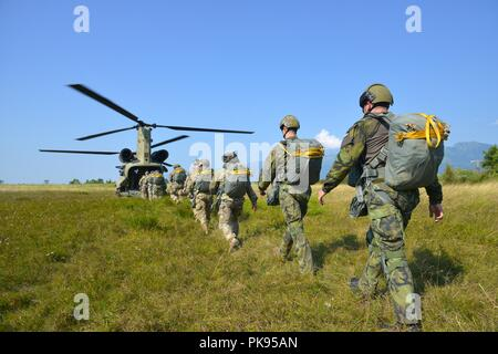 U.S. Army Paratroopers, assigned to the 2nd Battalion, 503rd Infantry Regiment, 173rd Airborne Brigade, along with Czechs Paratroopers, board a 12th Combat Aviation Brigade CH-47 Chinook helicopter for an airborne operation at Juliet Drop Zone, Pordenone, Italy, August 22, 2018, August 22, 2018. The combined exercise demonstrates the multinational capacity building of the airborne community and focused on enhancing NATO operational standards and developing individual technical skills. (U.S. Army photo by Paolo Bovo). () - Stock Photo