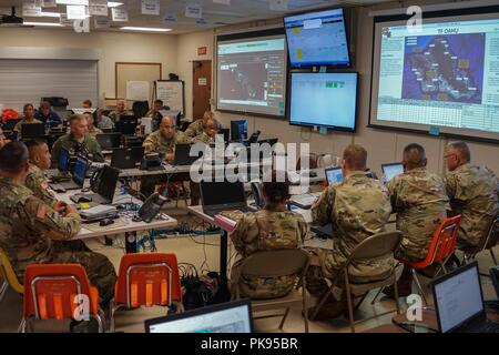 Service members with Joint Task Force 5-0 receive a daily commander's update brief, August 25, 2018 at the Hawaii Army National Guard Center at Diamond Head, Honolulu Hawaii, August 24, 2018. JTF 5-0 is a joint task force led by a dual status commander that is established to respond to the effects of Hurricane Lane on the state of Hawaii. The members of the task force remain committed to monitoring the effects and incidents across the state of Hawaii to respond to any requests made by Local and state authorities through FEMA. () - Stock Photo