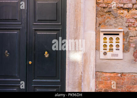 Ancient intercom in Venice with golden buttons, Italy. - Stock Photo