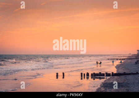 Surfers walk along the beach at sunset, April 3, 2015, in Folly Beach, South Carolina. (Photo by Carmen K. Sisson/Cloudybright) - Stock Photo