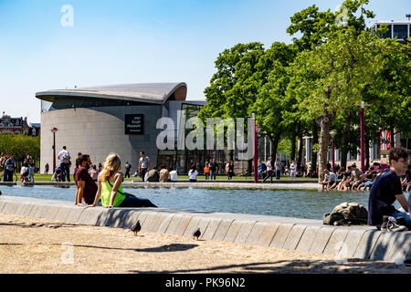 Tourists relaxing by the side of a pool, in the background the Van Gogh Museum. Amsterdam, Netherlands - Stock Photo