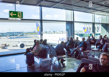Frankfurt, Germany - April 28, 2018: passengers sitting and waiting for departure inside of Frankfurt Pearson Airport at Frankfurt, Germany on April 28, 2018 - Stock Photo