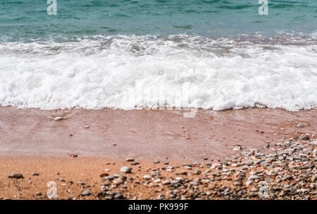 White fluffy waves hitting the colorful stones and peebles on a beach in summer - Stock Photo