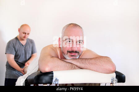 Massage relax studio. People enjoy a massage bed. Massage therapist working with patient, massaging his calves. Body care. Man having massage. - Stock Photo