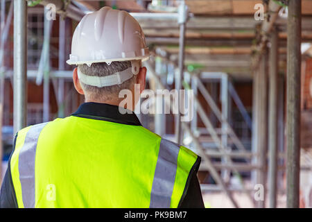 Rear view of male builder construction worker on building site wearing hard hat and hi-vis vest - Stock Photo