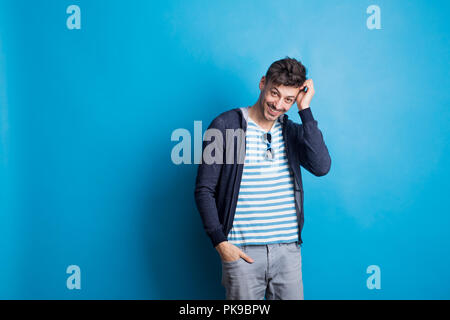 Portrait of a cheerful young man wearing casual clothes in a studio. - Stock Photo