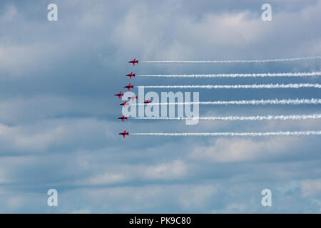 The RAF's Red Arrows display team in 'Lightning' formation against a heavy sky. - Stock Photo