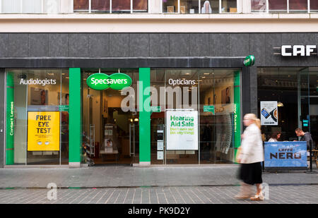 A woman walking past a Specsavers store in Church St Liverpool UK. - Stock Photo