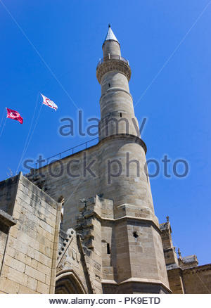 Minaret on a Mosque in Nicosia, Northern Cyprus with the Turkish Cypriot flags flying - Stock Photo