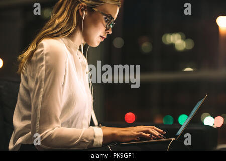 Young woman working late at office. Businesswoman using laptop in office lobby. - Stock Photo