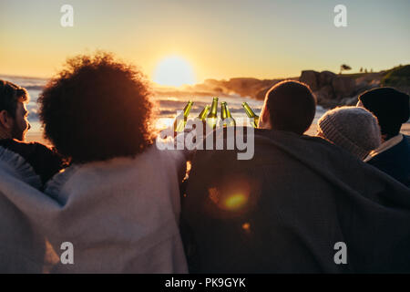 Group of friends cheers with beers at the beach. Young people sitting together at beach during sunset and having a party. - Stock Photo