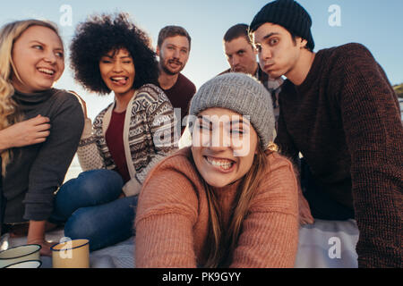 Group of young people making funny faces while taking selfie on the beach. Young people enjoying together at the beach making a self portrait. - Stock Photo