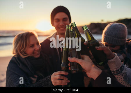 Young people toasting with beer bottles on beach. Group of men and women having drinks together at sea shore during sunset. - Stock Photo
