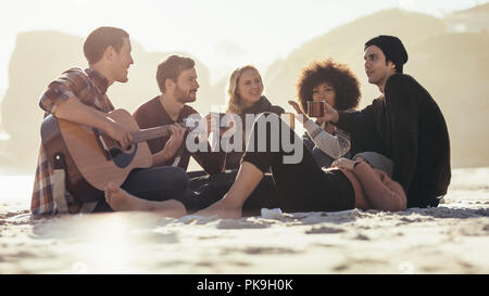 Young man playing guitar for friends on the beach. Group of friends having party at the seashore. - Stock Photo