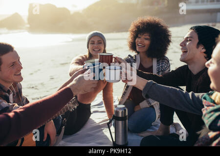 Group of multi-ethnic young people toasting coffee mugs on the beach. Group of friends spending time together at the beach having coffee. - Stock Photo
