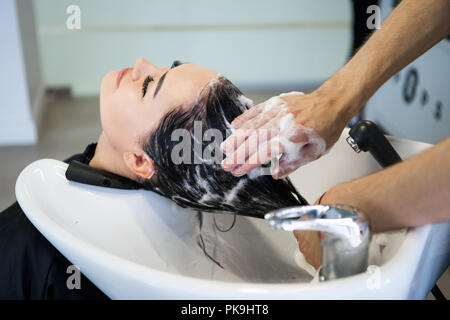Unrecognizable professional hairdresser washing hair to her client. Beautiful hairdresser washing hair to her client lady in hairdressing saloon. Client sitting with her eyes closed. - Stock Photo