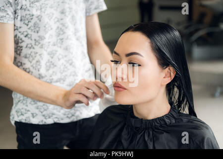 Hairdresser cutting woman's hair in salon, smiling, front view, close-up, portrait - Stock Photo