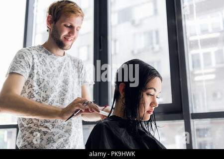 Young beautiful woman having her hair cut at the hairdresser's. Young male hairdresser smiling and making hairstyle to the customer. - Stock Photo