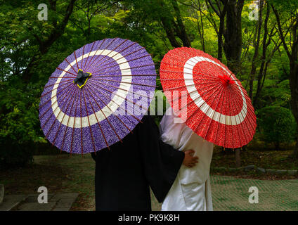 Japanese couple with umbrellas in the botanic garden, Kansai region, Kyoto, Japan - Stock Photo