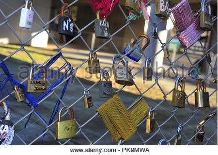 love token padlocks on a wire mesh fence - Stock Photo