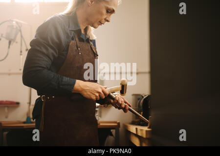 Professional female jeweler making jewelry using traditional tools in her workshop. Woman goldsmith making a ring at a workbench. - Stock Photo
