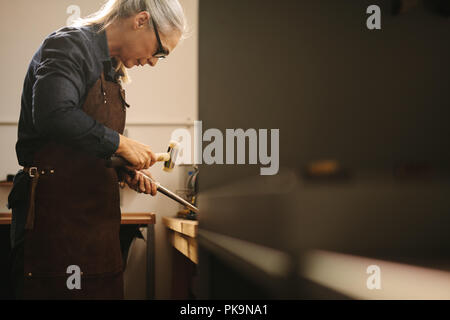 Senior woman making jewelry using traditional tools in her workshop. Female goldsmith wearing leather apron and glasses making a ring at a workbench u - Stock Photo