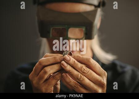 Woman goldsmith examining sliver designer ring using magnifying glass. Professional jeweler inspecting a ring using magnifying glass. - Stock Photo