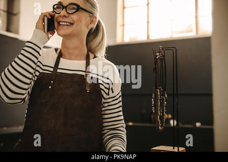 Portrait of happy senior woman wearing apron talking on mobile phone and smiling at jeweler workshop. Female goldsmith making phone call from her desi - Stock Photo