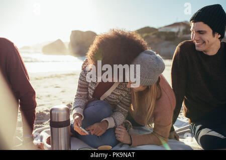 Two young woman sitting on the beach looking something funny on mobile phone and smiling with a friends sitting by. Group of young people relaxing on  - Stock Photo