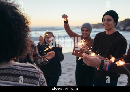 Diverse group of young people celebrating new year's day at the beach. Young people having fun with sparklers outdoors at the sea shore. - Stock Photo