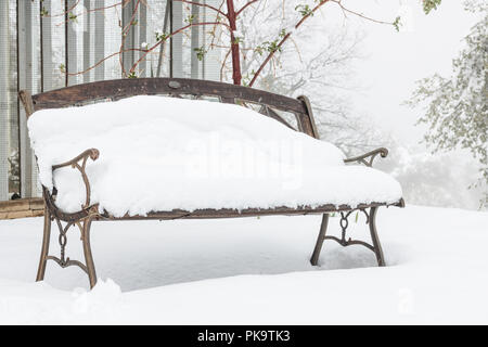 Snow covered empty vintage old garden bench on a col wet misty snowy day, iron work detail and old wood visible - Stock Photo
