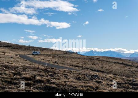 Camper van driving down mountain road in New Zealand - Stock Photo