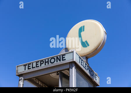 Telephone sign on phone booth; California, USA - Stock Photo