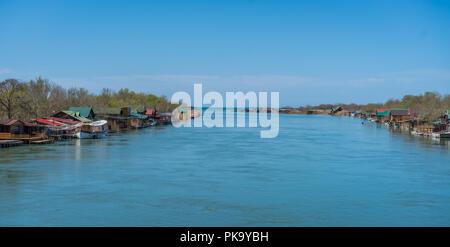 Small wooden houses and restaurants on the riverbank  of the Ada Bojana river near Ulcinj, Montenegro - Stock Photo