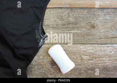White spot on the dress armpit and deodorant on a wooden background. Top view. - Stock Photo