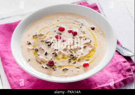 Mushroom soup in a plate with lingonberries on top - Stock Photo