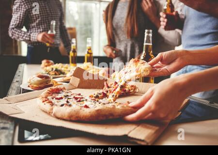 Friends taking slices of tasty pizza from plate, close up view. - Stock Photo
