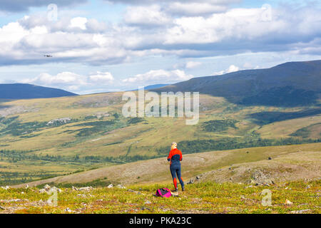 Girl playing drone in mountain - Stock Photo
