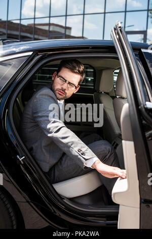 side view of pensive businessman looking away while sitting on backseat with opened car door - Stock Photo